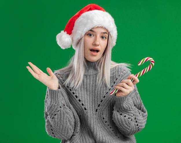 Giovane donna bionda in maglione invernale e cappello santa tenendo il bastoncino di zucchero guardando la telecamera confusa con il braccio alzato in piedi su sfondo verde