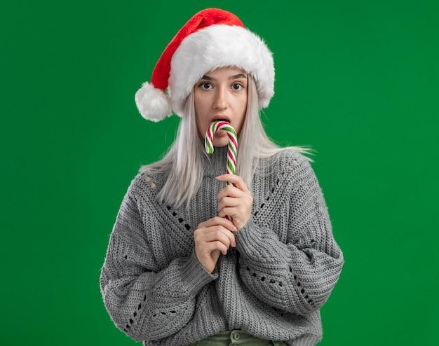 Giovane donna bionda in maglione invernale e cappello da babbo natale che tiene in mano un bastoncino di zucchero con la faccia seria che lo assaggerà in piedi sul muro verde