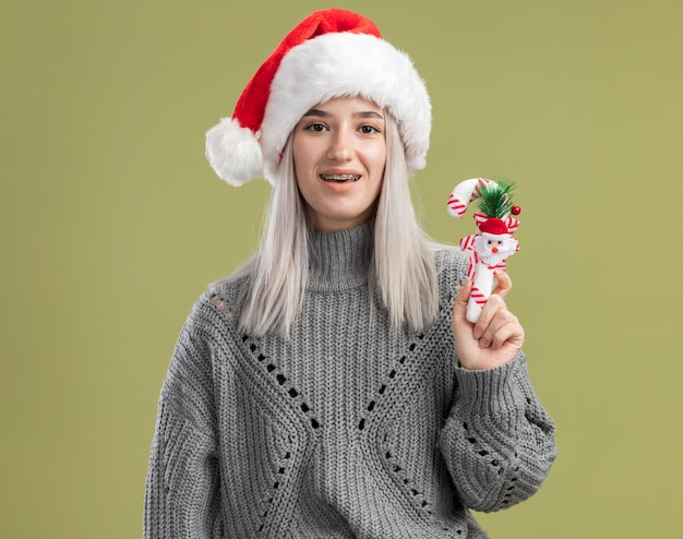 Young blonde woman in winter sweater and santa hat holding christmas candy cane  happy and excited  standing over green wall