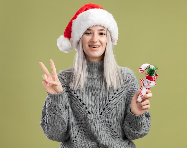 Young blonde woman in winter sweater and santa hat holding christmas candy cane  smiling cheerfully showing v-sign  standing over green wall