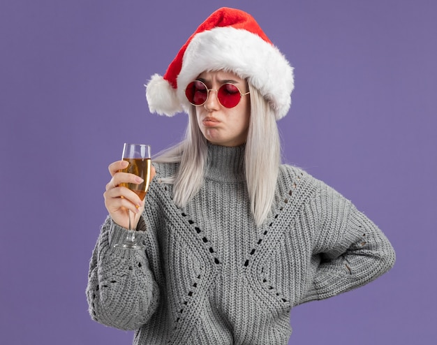 Young blonde woman in winter sweater and santa hat holding glass of champagne  looking at it confused and displeased  standing over purple  wall