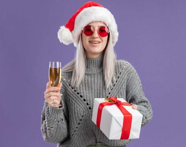Young blonde woman in winter sweater and santa hat holding a present and glass of champagne  with smile on happy face  standing over purple  wall