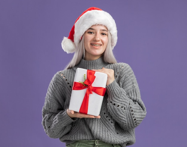 Young blonde woman in winter sweater and santa hat holding a present  with smile on happy face  standing over purple  wall