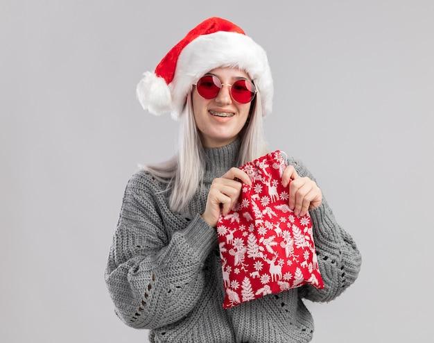 Giovane donna bionda in maglione invernale e cappello da babbo natale che tiene in mano una borsa rossa con regali di natale con un sorriso sul viso in piedi su un muro bianco white