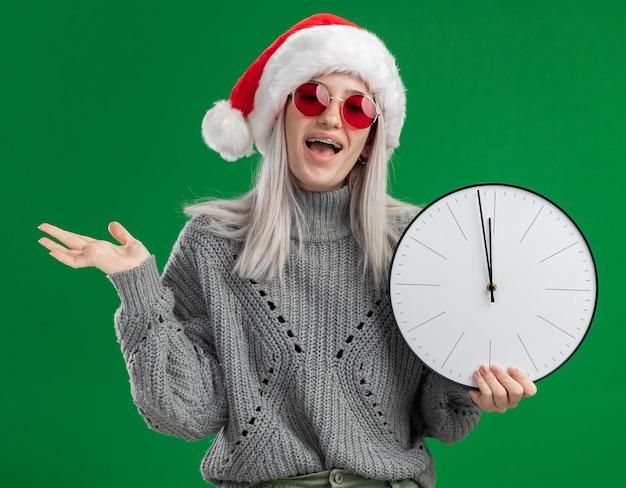 Giovane donna bionda in maglione invernale e cappello santa indossando occhiali rossi tenendo l'orologio da parete guardando la fotocamera in piedi felice ed eccitato su sfondo verde