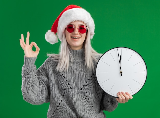 Giovane donna bionda in maglione invernale e santa hat indossando occhiali rossi tenendo l'orologio da parete guardando la telecamera sorridendo allegramente mostrando segno ok in piedi su sfondo verde