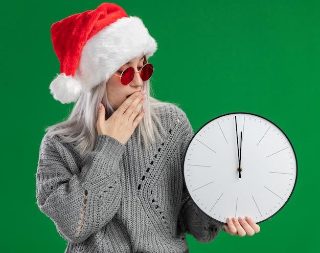 Giovane donna bionda in maglione invernale e santa hat indossando occhiali rossi tenendo l'orologio da parete guardando stupito che copre la bocca con la mano in piedi su sfondo verde