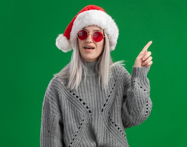 Giovane donna bionda in maglione invernale e cappello da babbo natale con gli occhiali rossi che sembrano sorpresi mostrando il dito indice con una nuova idea in piedi su sfondo verde