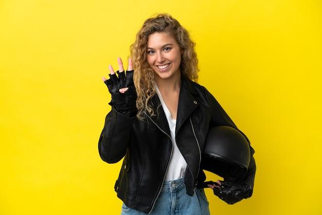 노란색 배경에 오토바이 헬멧을 쓴 젊은 금발 여성이 행복하고 손가락으로 4를 세고 있다
