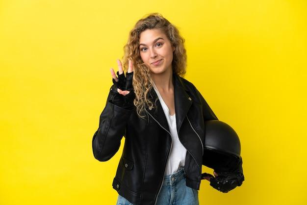 幸せな黄色の背景に分離されたオートバイのヘルメットと指で3を数える若いブロンドの女性