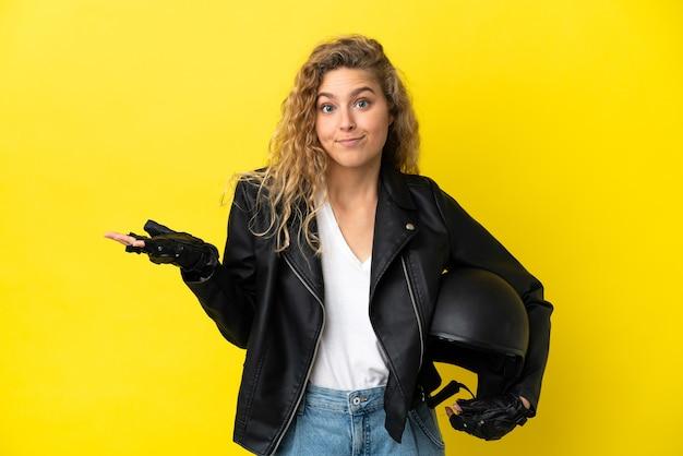 Молодая блондинка с мотоциклетным шлемом, изолированным на желтом фоне, сомневается, поднимая руки