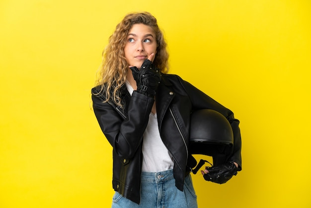 Молодая блондинка с мотоциклетным шлемом, изолированные на желтом фоне, сомневаясь