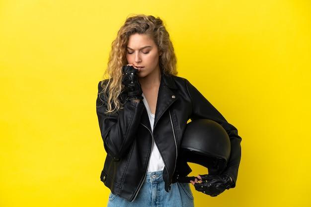 노란색 배경에 오토바이 헬멧을 쓴 젊은 금발 여성이 의심을 품고 있다