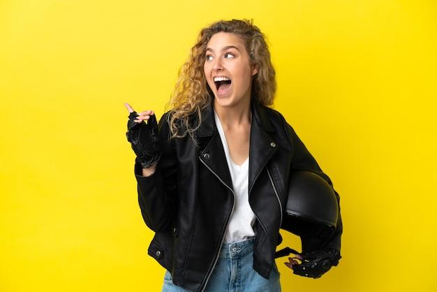 Молодая блондинка с мотоциклетным шлемом изолирована на желтом фоне, намереваясь реализовать решение, подняв палец вверх