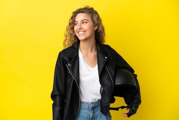 Молодая блондинка с мотоциклетным шлемом, изолированные на желтом фоне, глядя в сторону
