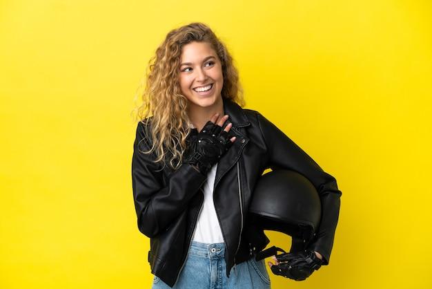 노란색 배경에 오토바이 헬멧을 쓴 젊은 금발 여성이 웃고 있는 동안 올려다보고 있다