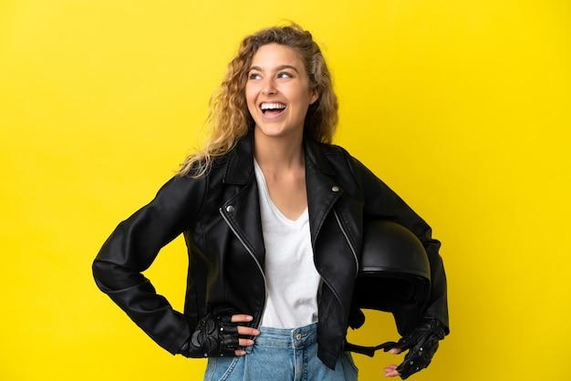 노란색 배경에 오토바이 헬멧을 쓴 젊은 금발 여성이 팔짱을 끼고 웃고 있다