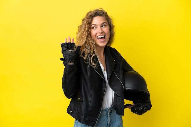 노란색 배경에 격리된 오토바이 헬멧을 쓴 젊은 금발 여성이 행복한 표정으로 손으로 경례를 하고 있다