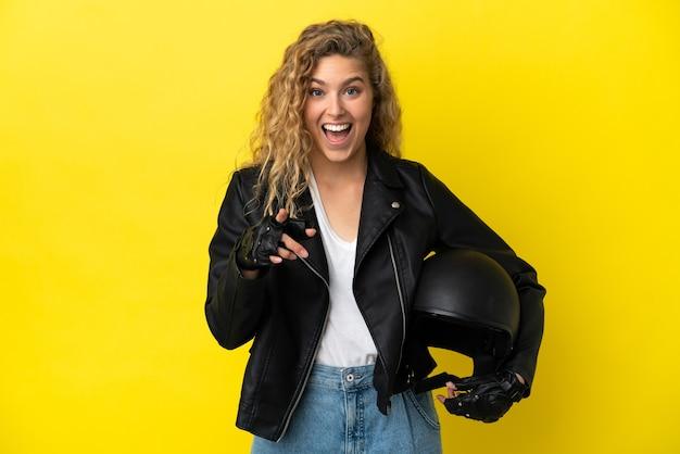 노란색 배경에 오토바이 헬멧을 쓴 젊은 금발 여성이 놀라 앞을 가리키고 있다