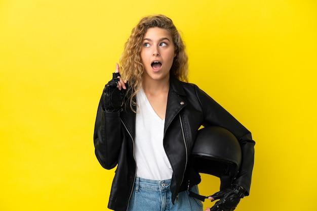 Молодая блондинка с мотоциклетным шлемом, изолированные на желтом фоне, думает об идее, указывая пальцем вверх