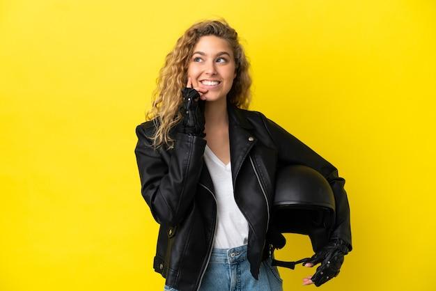 Молодая блондинка в мотоциклетном шлеме изолирована на желтом фоне, думая об идее, глядя вверх