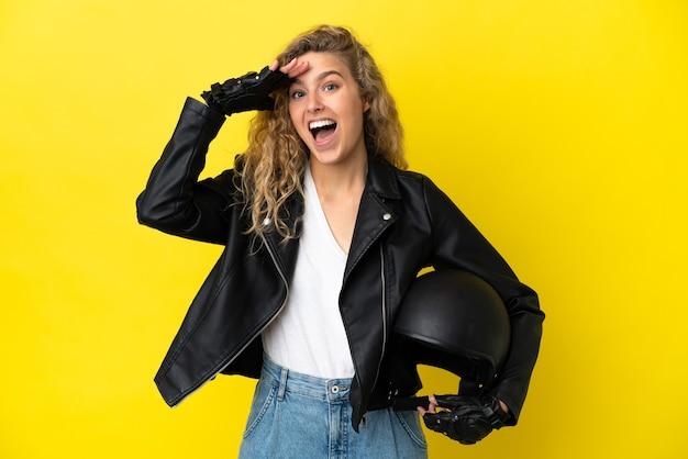 Молодая блондинка в мотоциклетном шлеме изолирована на желтом фоне с удивленным выражением лица