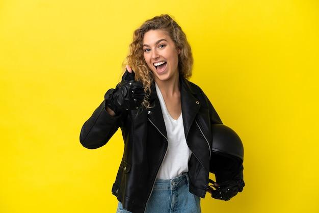Молодая блондинка с мотоциклетным шлемом изолирована на желтом фоне с большими пальцами руки вверх, потому что произошло что-то хорошее