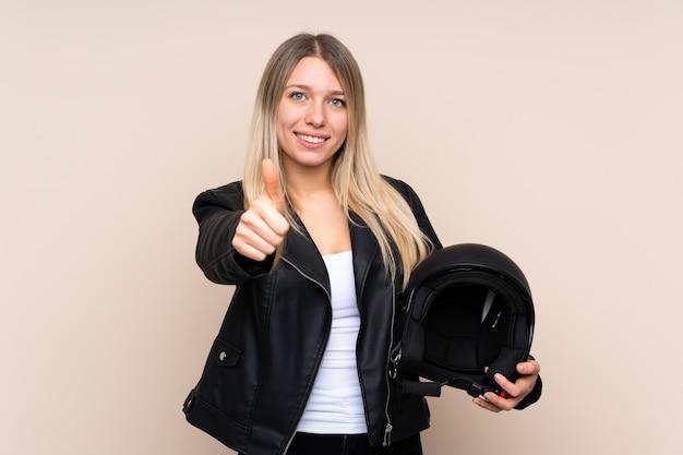 ジェスチャー親指を与える上オートバイヘルメットを持つ若いブロンドの女性