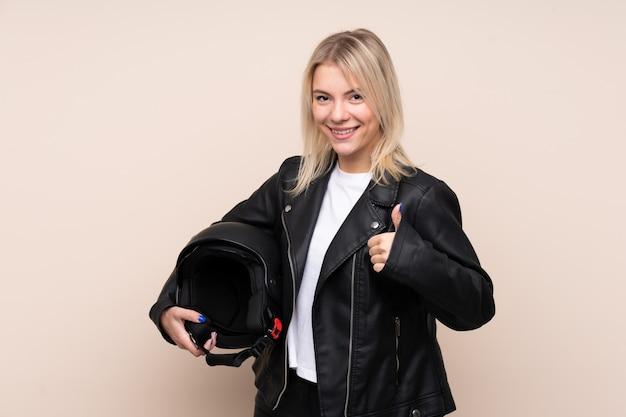 何か良いことが起こったので親指で隔離された壁の上のオートバイのヘルメットを持つ若いブロンドの女性