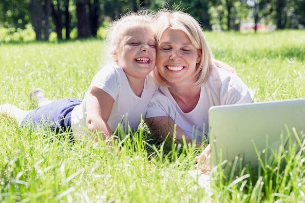 小さな娘と若いブロンドの女性はラップトップで公園の芝生に寝転んで、笑って、日当たりの良い夏の日に楽しんでください。