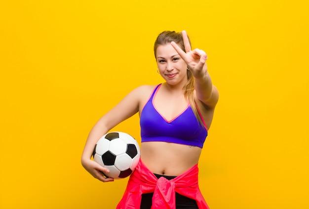 サッカーボールを持つ若いブロンドの女性。スポーツコンセプト