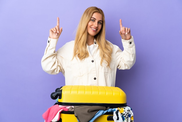 Молодая блондинка с чемоданом, полным одежды, над изолированной фиолетовой стеной, указывая на отличную идею