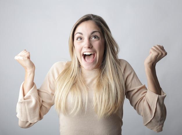 白の後ろに幸せの感情を示す開いた口を持つ若いブロンドの女性