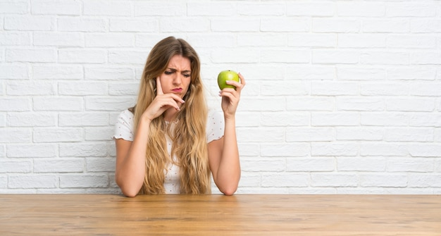 Young blonde woman with an apple having doubts