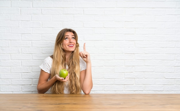 Young blonde woman with an apple pointing up