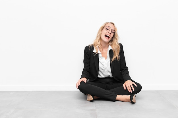 Young blonde woman with a big, friendly, carefree smile, looking positive, relaxed and happy, chilling sitting on the floor