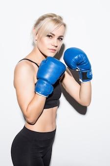 Giovane donna bionda con guantoni da boxe blu pronti a combattere su bianco