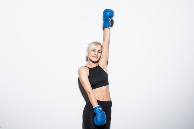 Young blonde woman with blue boxing gloves on white victory hand up
