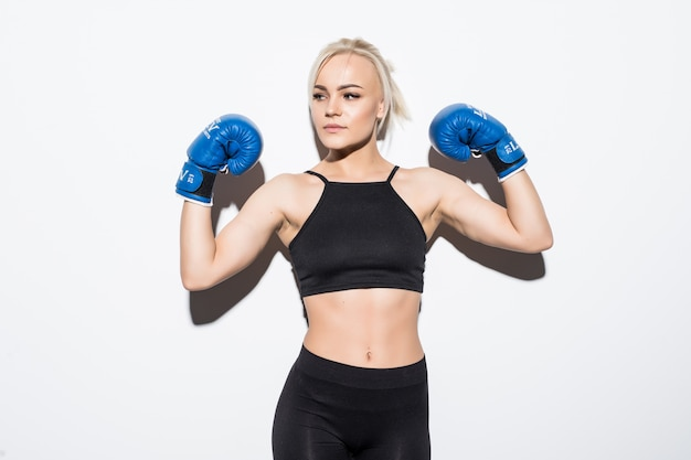 Young blonde woman with blue boxing gloves on white