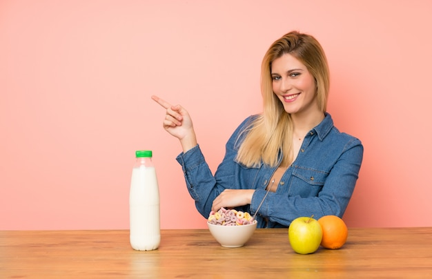 Young blonde woman with bowl of cereals pointing finger to the side