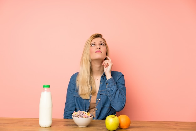 Young blonde woman with bowl of cereals standing and thinking an idea
