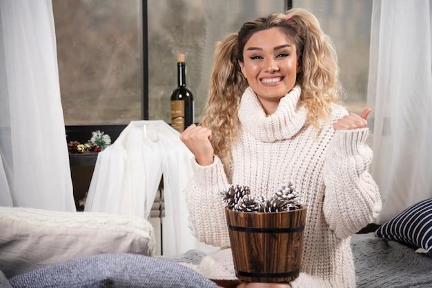 Giovane donna bionda con secchio di pigne nelle quali sentirsi felice.