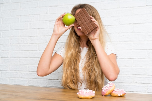 Young blonde woman with chocolat and an apple