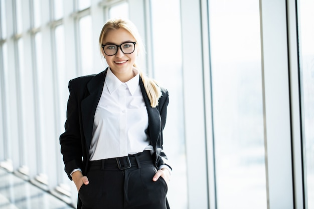 Young blonde woman with crossed hands is standing in the corner panoramic office.
