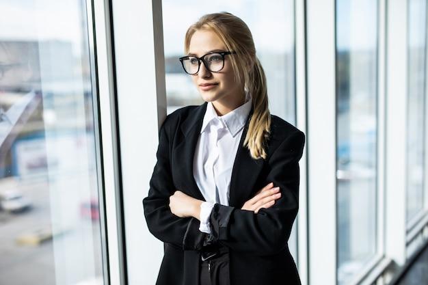 交差した手で若いブロンドの女性が隅にあるパノラマのオフィスに立っています。