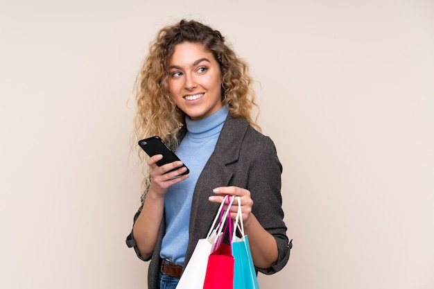 Young blonde woman with curly hair on beige wall holding shopping bags and a mobile phone
