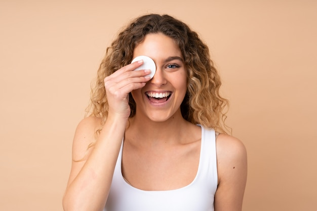 Young blonde woman with curly hair on beige wall with cotton pad for removing makeup from her face and smiling