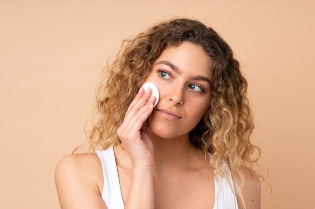 Young blonde woman with curly hair on beige wall with cotton pad for removing makeup from her face