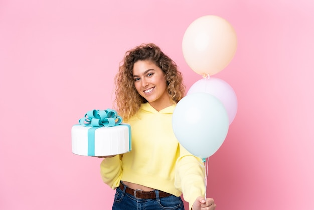 多くの風船をキャッチし、ピンクの壁に分離された大きなケーキを保持している巻き毛の若いブロンドの女性