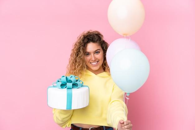 Молодая блондинка с вьющимися волосами ловит много воздушных шаров и держит большой торт, изолированный на розовом
